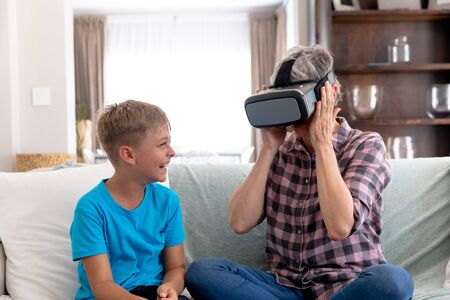 Senior Caucasian woman spending time at home together with her grandson, sitting on a couch in the sitting room and using a VR headset.