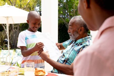 African American boy showing his grandfather his homework during a family lunch in the garden on a sunny day. Standard-Bild