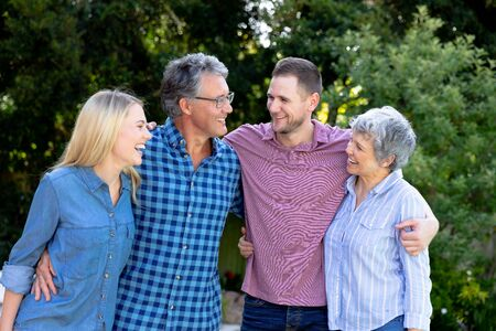 Senior Caucasian couple and their adult son and daughter spending time together in the garden on a sunny day, embracing, smiling and interacting.