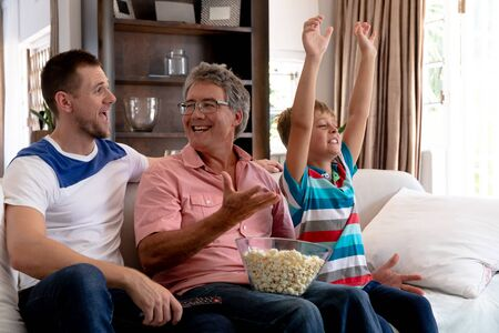 Senior Caucasian man spending time with his son and his grandson at home in the sitting room, watching together television.