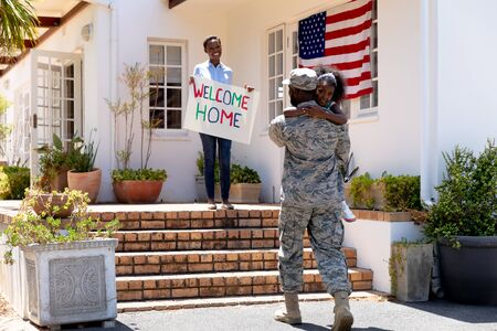 African American woman and her daughter welcoming an African American solider wearing uniform, embracing by their house on a sunny day.