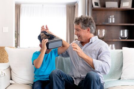 Senior Caucasian man spending time at home together with his grandson, sitting on a couch in the sitting room and using a VR headset.