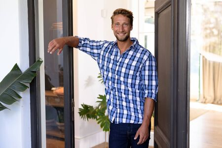 Caucasian man enjoying his time at home, standing at his open front door, greeting a visitor, looking at the camera and smiling Banque d'images