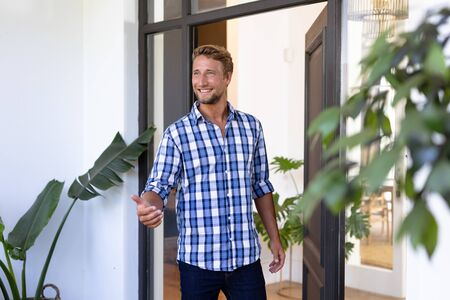 Caucasian man enjoying his time at home, standing at his open front door, greeting a visitor, looking away from the camera and smiling