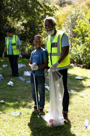 Senior African American man spending time outside with his family, embracing his grandson, looking at the camera and smiling, wearing blue volunteers t shirts, collecting garbage, holding a garbage bag, on a sunny day 版權商用圖片