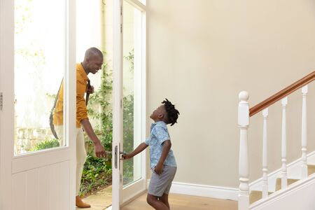 Side view of an African American man arriving home, welcomed by his young son opening the front door Reklamní fotografie