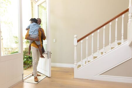 Front view of an African American man arriving home carrying his young son through the open front door into the hallway Reklamní fotografie