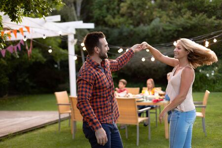 Side view of a Caucasian couple in the garden, having fun holding hands, dancing and smiling at each other, their son and daughter sitting at a table with garden lights on in the background