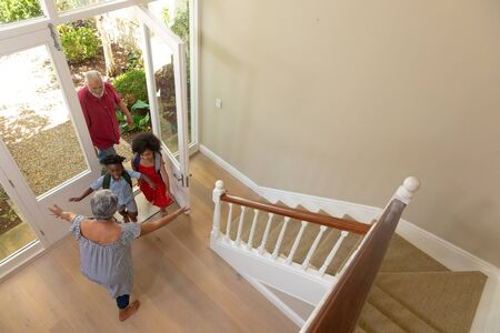 High angle view of a mixed race senior man arriving home with his grandson and granddaughter, greeted by their grandmother, standing with open arms in the hallway of their home