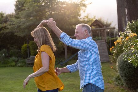 Side view of a senior Caucasian couple having fun holding hands and dancing in the garden on a sunny day