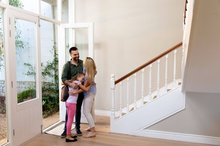 Side view of a Caucasian couple and their daughter embracing in the hallway of their house at the front door, the daughter is wearing a backpack Reklamní fotografie
