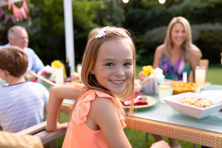 Portrait of a Caucasian girl sitting at a table and turning to camera smiling during a meal outside in the garden with her multi-generation family