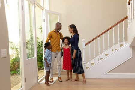 Front view of a mixed race couple and their young son and daughter standing in the hallway of their new home talking, the father just arrived through the open front door has his arms around both children