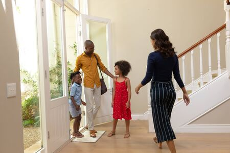 Front view of an African American man arriving home with his son and walking through the front door, greeted by his wife and daughter in the hallway