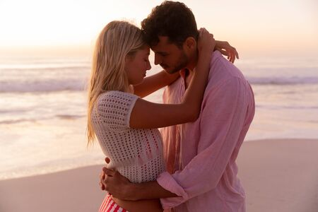 Caucasian couple enjoying time at the beach, embracing and touching their foreheads with their eyes closed