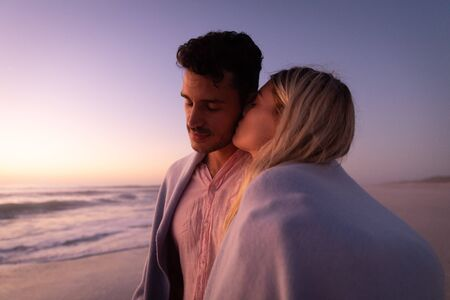 Caucasian couple enjoying time at the beach, embracing and covering themselves with a blanket, a woman is kissing a man on his cheek
