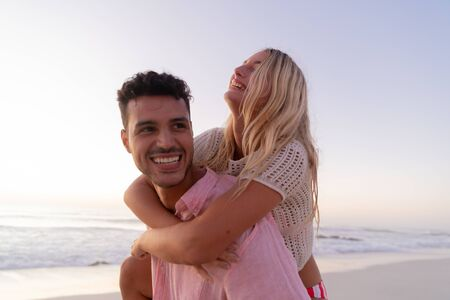 Caucasian couple enjoying time at the beach, a man is holding a woman piggy back