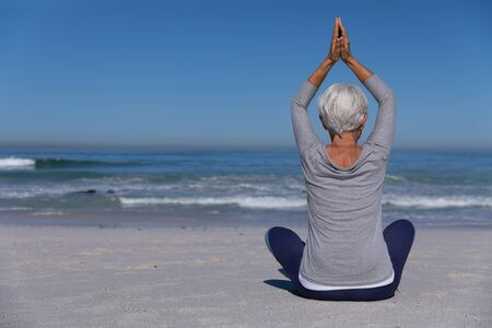 Senior Caucasian woman enjoying time at the beach on a sunny day, sitting on sand and practising yoga with sea in the background