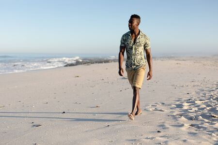 Attractive African American man enjoying free time on beach on a sunny day, wearing a Hawaiian shirt, walking on the beach sun shining on his face. Relaxing summer vacation.