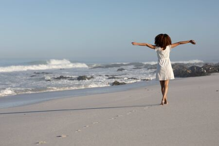A rear view of a happy, attractive mixed race woman with her arms outstretched enjoying free time on beach on a sunny day, wearing a white dress, walking, sun shining behind her. Relaxing summer vacation.