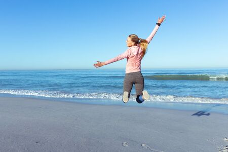 A happy Caucasian woman wearing sports clothes, enjoying time at the beach on a sunny day, jumping, facing the sea