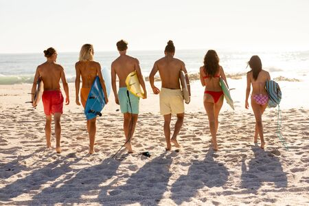 A multi-ethnic group of friends enjoying their time together on a beach on a sunny day, walking towards the sea in a row, holding surfboards