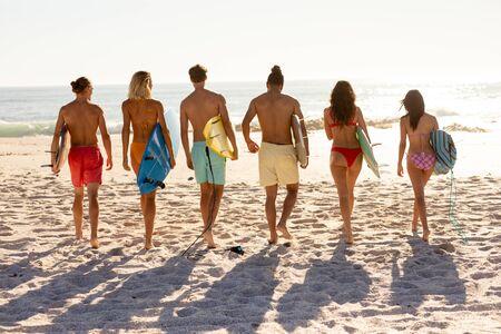 Un groupe d'amis multiethniques profitant de leur temps ensemble sur une plage par une journée ensoleillée, marchant vers la mer d'affilée, tenant des planches de surf