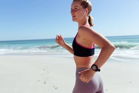 A Caucasian woman wearing sports clothes, enjoying time at the beach on a sunny day, exercising, running along the beach, with sea in the background Stok Fotoğraf