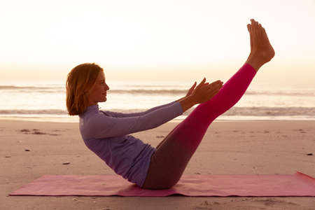 Attractive blonde Caucasian woman enjoying time at the beach at sundown, practicing yoga, stretching in yoga position, with sunset sky and sea in the background. Summer tropical beach vacation. Stok Fotoğraf