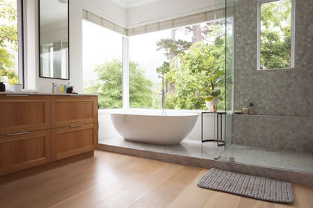 Modern bathroom interior showing free standing bath with large windows showing green trees and plants outside, with white bathtub and silver water tap, grey shower and a table with a plant. Imagens