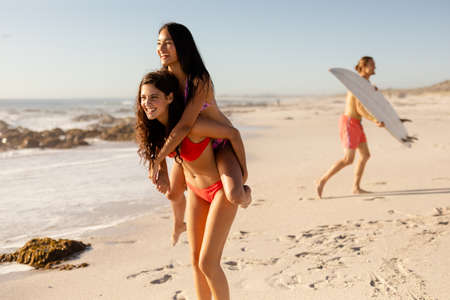 A Caucasian and an Asian female friend hanging out on a sunny beach wearing bikinis having fun piggybacking and smiling, a man carrying a surfboard in the background. Relaxing tropical beach holiday