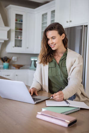 A Caucasian woman spending time at home, using her laptop, working from home. Lifestyle at home isolating, social distancing in quarantine lockdown during coronavirus covid 19 pandemic.