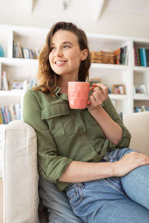 Caucasian woman spending time at home, sitting on sofa, drinking coffee from a mug. Lifestyle at home isolating, social distancing in quarantine lockdown during coronavirus covid 19 pandemic.