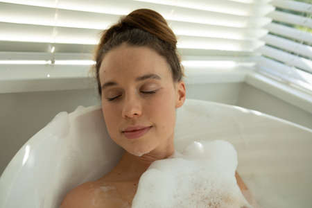 A Caucasian woman spending time at home, having a foamy bath, relaxing. Lifestyle at home isolating, social distancing in quarantine lockdown during coronavirus covid 19 pandemic.
