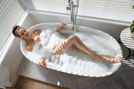 A Caucasian woman spending time at home, relaxing, having a foamy bath. Lifestyle at home isolating, social distancing in quarantine lockdown during coronavirus covid 19 pandemic.