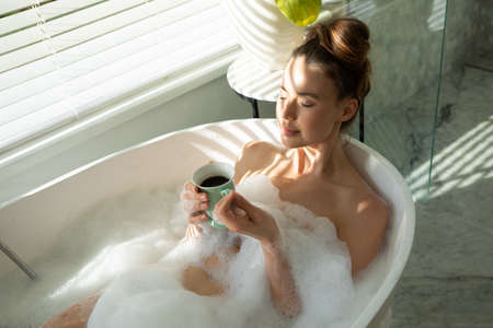 A Caucasian woman spending time at home, having a foamy bath, drinking coffee. Lifestyle at home isolating, social distancing in quarantine lockdown during coronavirus covid 19 pandemic.