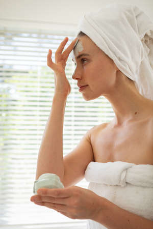 A Caucasian woman spending time at home, wearing a towel, putting face pack on. Lifestyle at home isolating, social distancing in quarantine lockdown during coronavirus covid 19 pandemic.