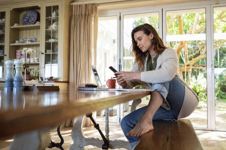 A Caucasian woman spending time at home, using her laptop and smartphone, working from home. Lifestyle at home isolating, social distancing in quarantine lockdown during coronavirus covid 19 pandemic.
