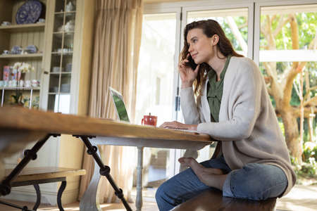 A Caucasian woman spending time at home, using her laptop and talking on the phone. Lifestyle at home isolating, social distancing in quarantine lockdown during coronavirus covid 19 pandemic.