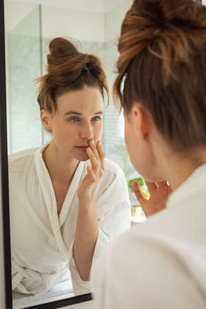 A Caucasian woman spending time at home, touching her face, looking in the mirror. Lifestyle at home isolating, social distancing in quarantine lockdown during coronavirus covid 19 pandemic.
