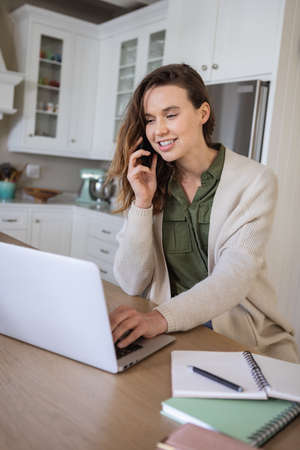 Caucasian woman spending time at home, using her laptop, working from home, talking on phone. Lifestyle at home isolating, social distancing in quarantine lockdown during coronavirus covid 19 pandemic Standard-Bild