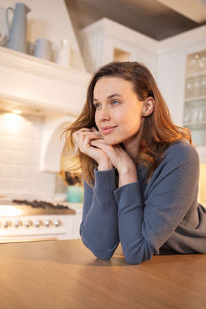 Caucasian woman spending time at home, sitting in the kitchen, smiling. Lifestyle at home isolating, social distancing in quarantine lockdown during coronavirus covid 19 pandemic. Standard-Bild