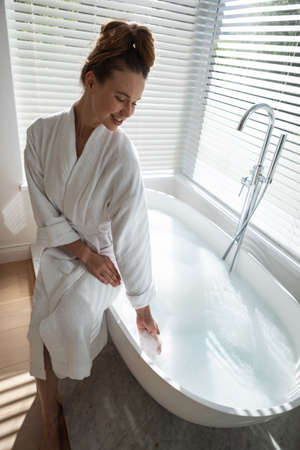 A Caucasian woman spending time at home, wearing a bathrobe, sitting on the bathtub. Lifestyle at home isolating, social distancing in quarantine lockdown during coronavirus covid 19 pandemic. Standard-Bild