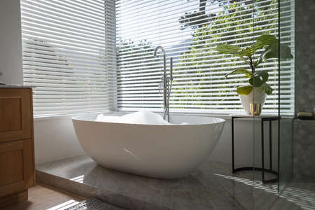 Modern bathroom interior showing free standing bath with large windows showing green trees and plants outside, with white bathtub and silver water tap, grey shower and a table with a plant.