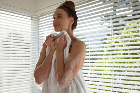 A Caucasian woman spending time at home, getting out of a foamy bath, holding a towel. Lifestyle at home isolating, social distancing in quarantine lockdown during coronavirus covid 19 pandemic.