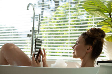 A Caucasian woman spending time at home, having a foamy bath, using her smartphone. Lifestyle at home isolating, social distancing in quarantine lockdown during coronavirus covid 19 pandemic.