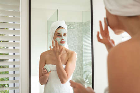 A Caucasian woman spending time at home, looking in the mirror, putting face pack on. Lifestyle at home isolating, social distancing in quarantine lockdown during coronavirus covid 19 pandemic.