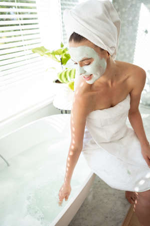 A Caucasian woman spending time at home, wearing a towel with a face pack on. Lifestyle at home isolating, social distancing in quarantine lockdown during coronavirus covid 19 pandemic. Standard-Bild