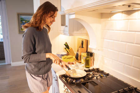 A Caucasian woman spending time at home, cooking in the kitchen. Lifestyle at home isolating, social distancing in quarantine lockdown during coronavirus covid 19 pandemic.
