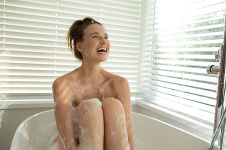 A Caucasian woman spending time at home, having a foamy bath, smiling. Lifestyle at home isolating, social distancing in quarantine lockdown during coronavirus covid 19 pandemic.